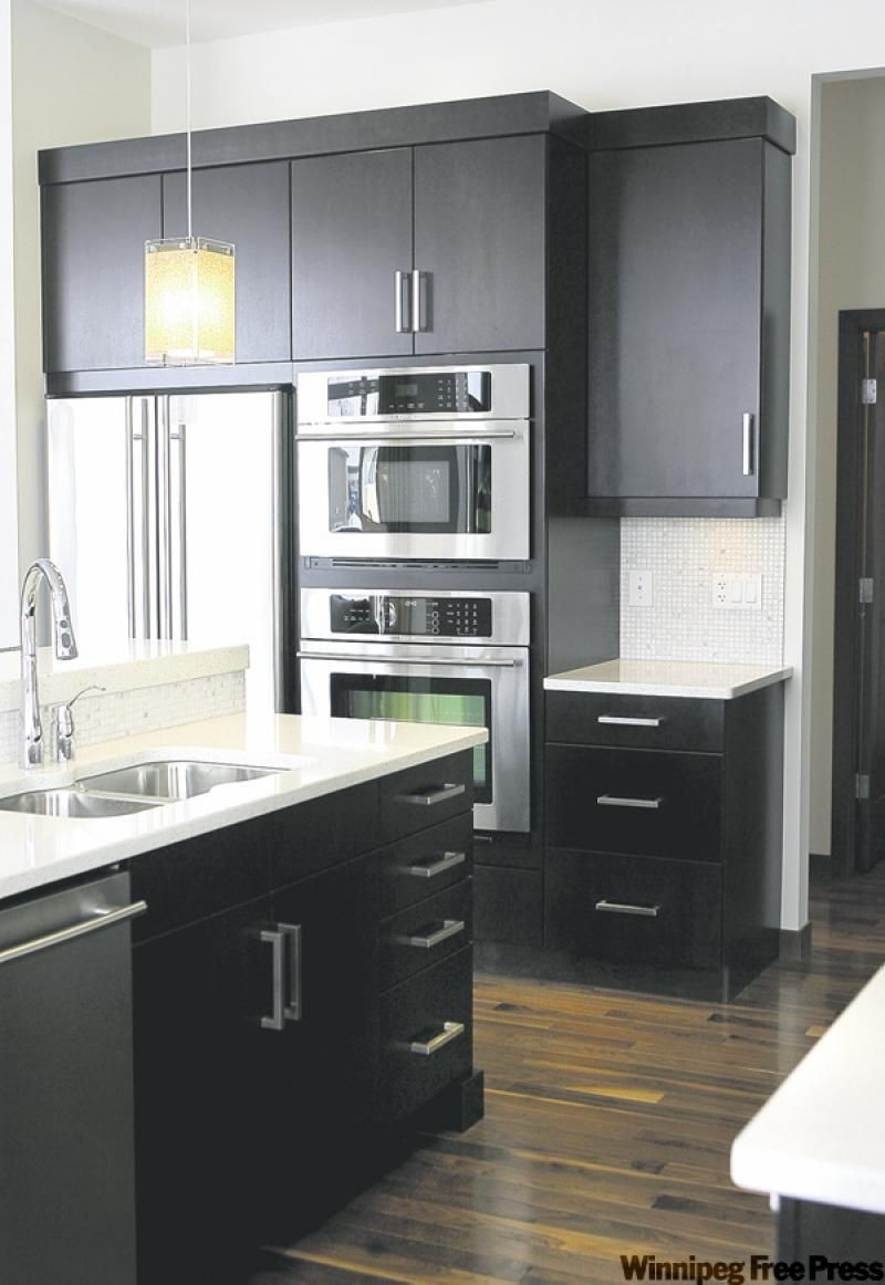 Dark expresso cabinets topped with white quartz countertops create ...