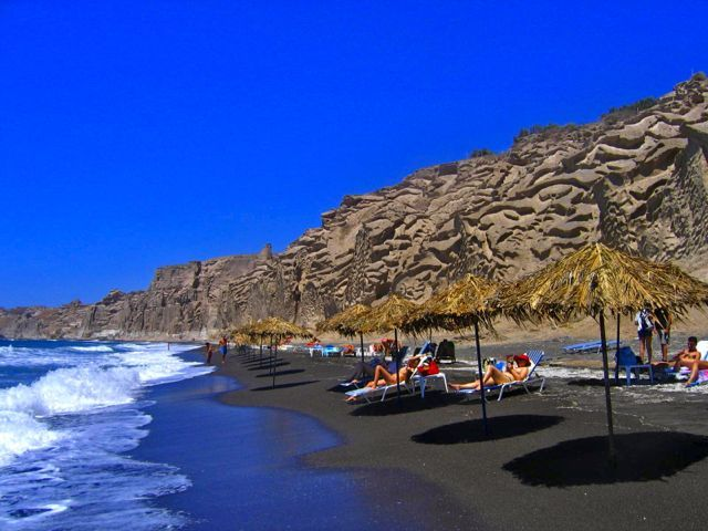 Vlychada Beach 10 Km S South Of Fira A Black Sand That Like All Beaches On Santorini Gets Very Hot During The Day So Wear Sandals
