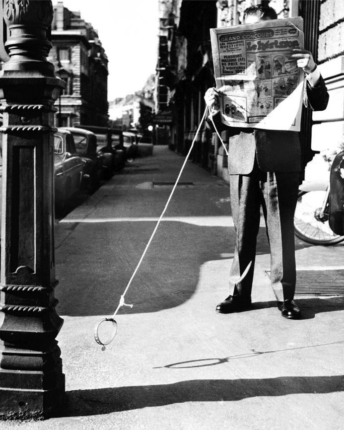 A man walking an invisible dog in the street while reading the newspaper, france, 1900-1909. © keystone-france/ gamma-keystone/ getty images.