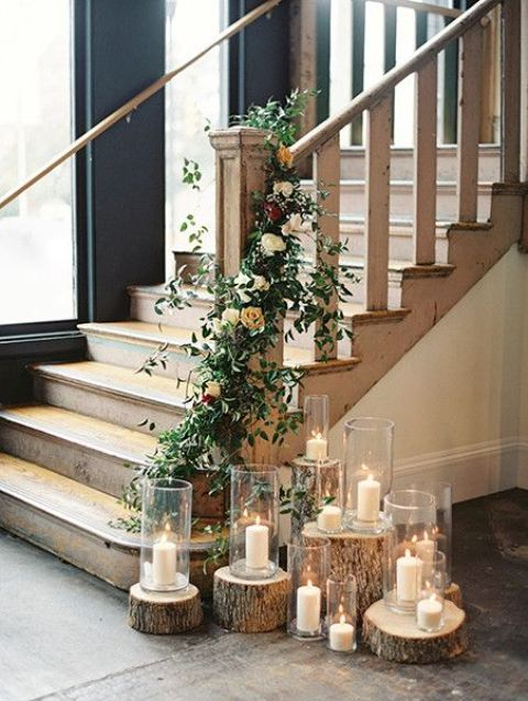 Tree stumps with candles and a greenery and orange rose garland that tree stumps with candles and a greenery and orange rose garland that interweaves the stairs junglespirit Choice Image