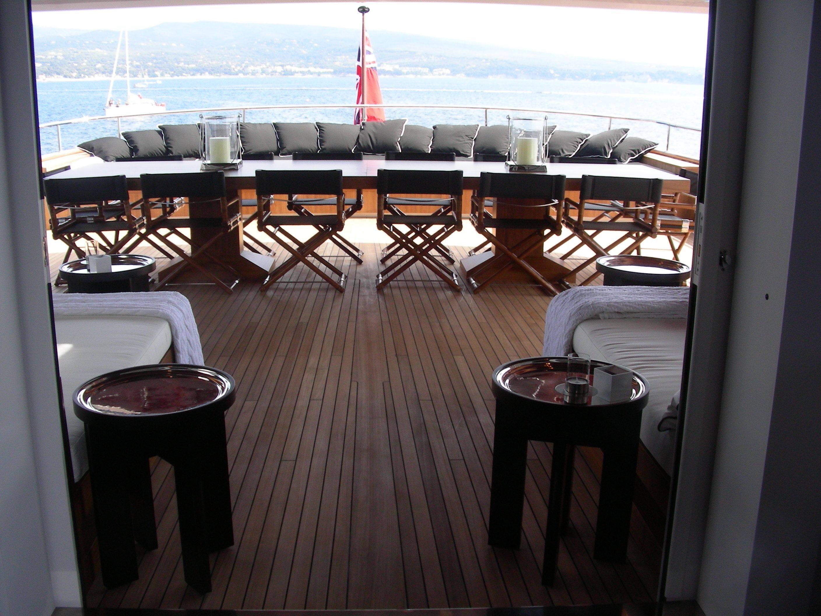 This yacht's bar deck seats 14 in black leather director's chairs around a teak dining table with chrome hurricane lanterns.