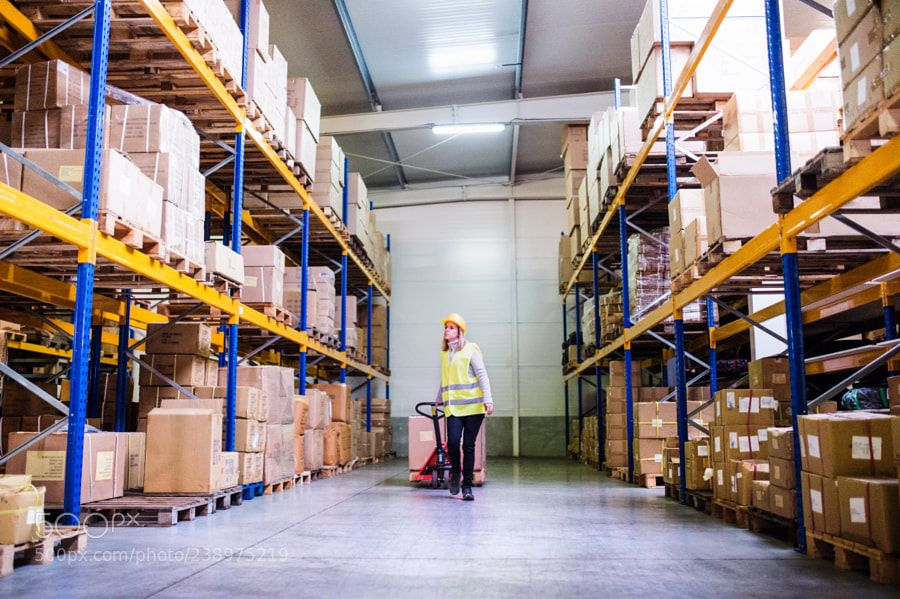Woman Warehouse Worker With Hand Forklift Truck  City And