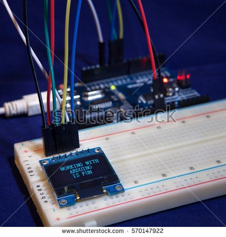 educational table top experiment with popular Arduino micro-controller and small OLED display saying: working with Arduino is fun.