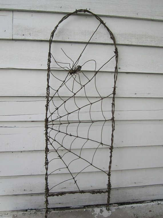 spider spinning a web barbed wire garden trellis made to