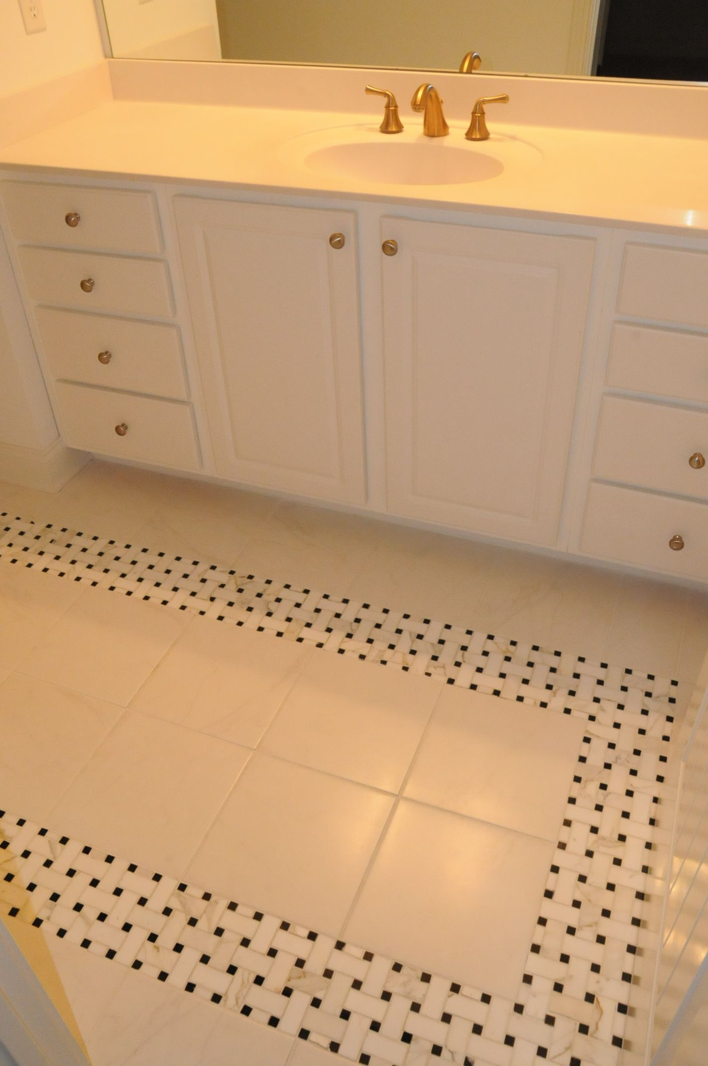 White tile laid straight with black and white woven border.