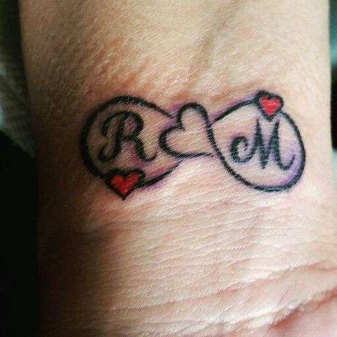Tatuaggio con lettere iniziali da innamorati , Tatuaggio con iniziali di  nomi intrecciate con cuore e simbolo dell\u0027infinito.