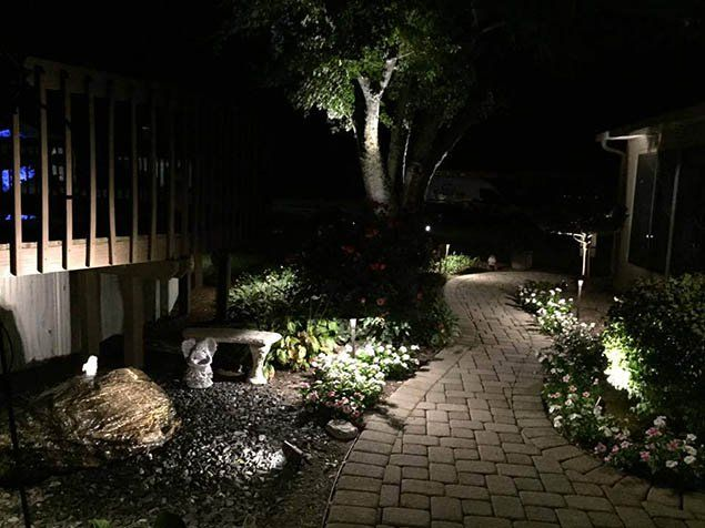 a back yard is lit by outdoor lighting in this this