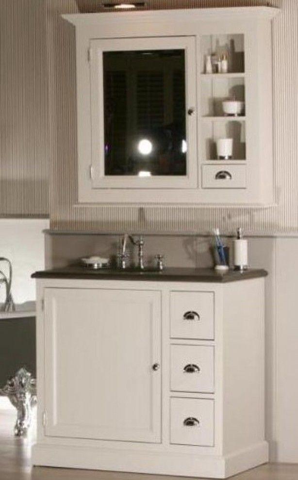 landelijk badkamer meubel met spiegelkast waarvan de spiegel deur ...