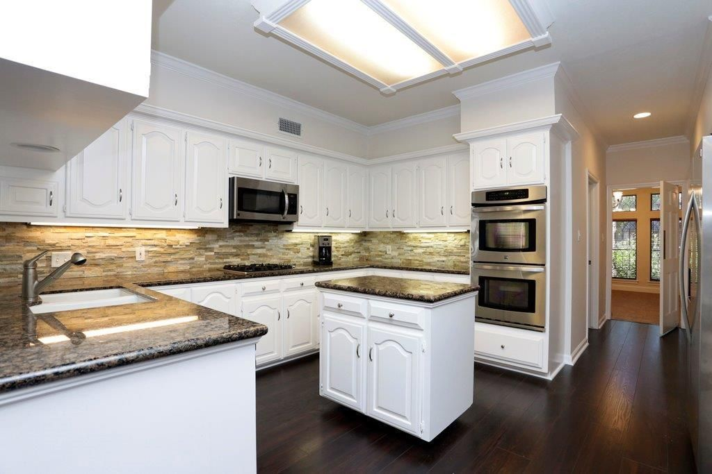 White Cabinets Stack Stone Backsplash And Granite Countertops