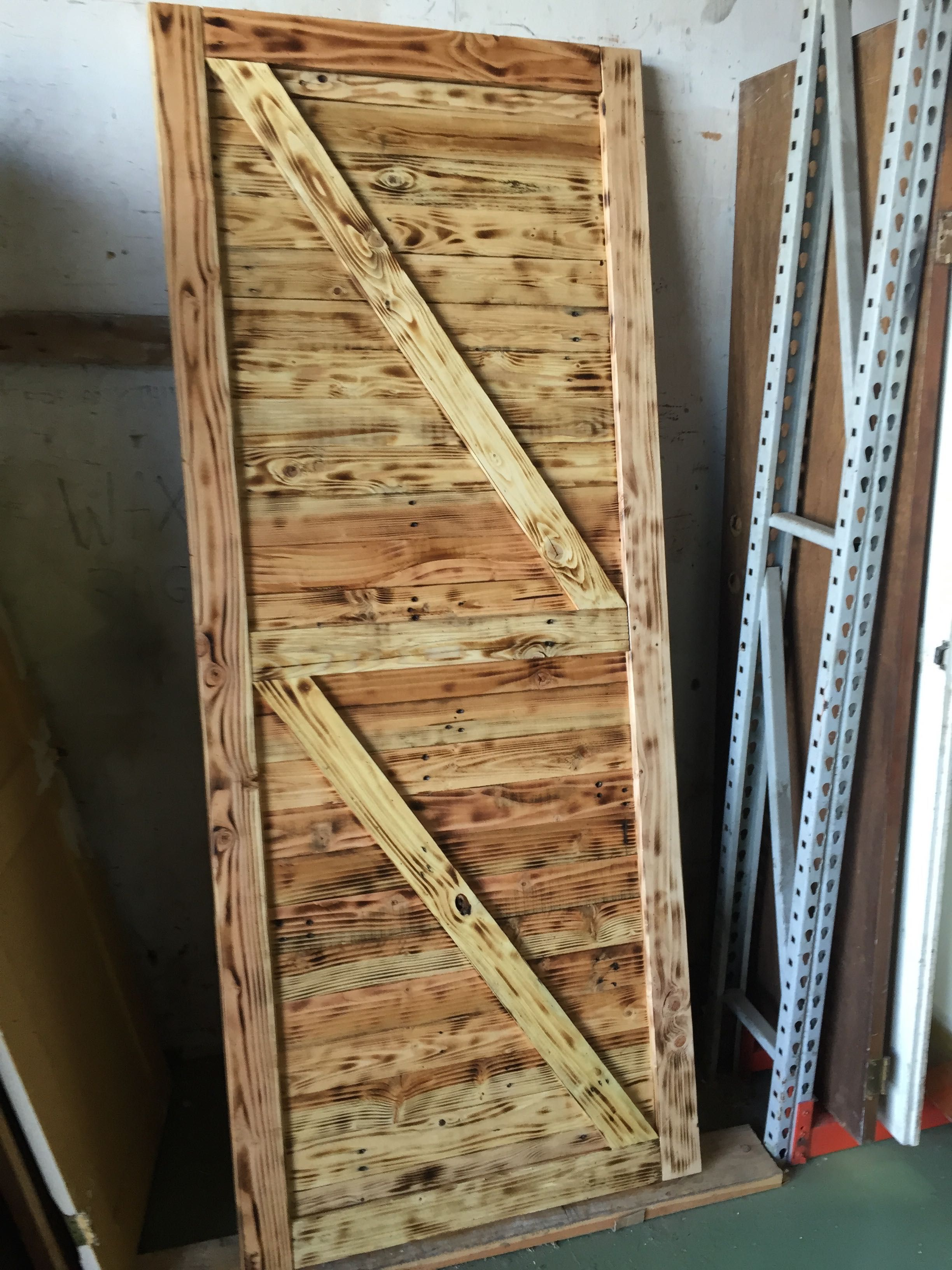 Rustic Farmhouse Style Barn Door With Burnt Wood And Z Bracing Located In San Diego Custom Barn Doors Rustic Farmhouse Style Barn Door