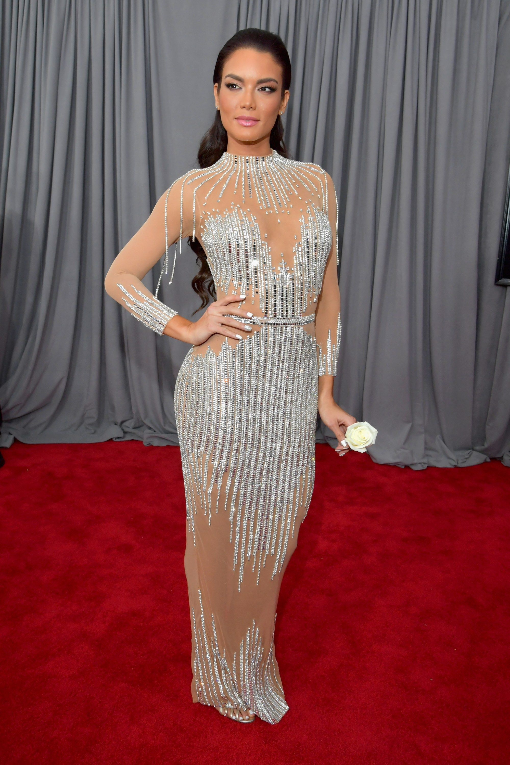 Zuleyka Rivera in a long silver beaded gown carrying a white rose on ...