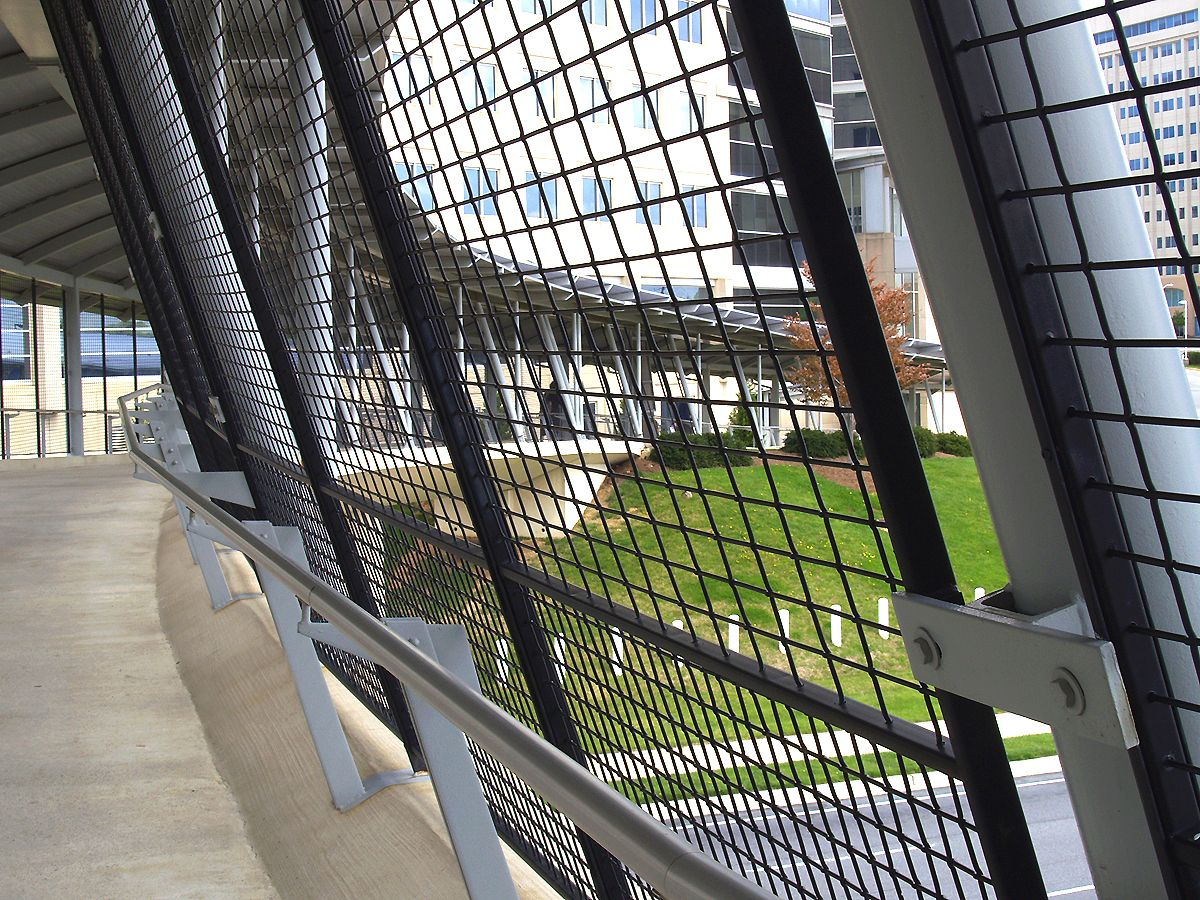 The woven wire mesh fence panels for this pedestrian bridge create a ...