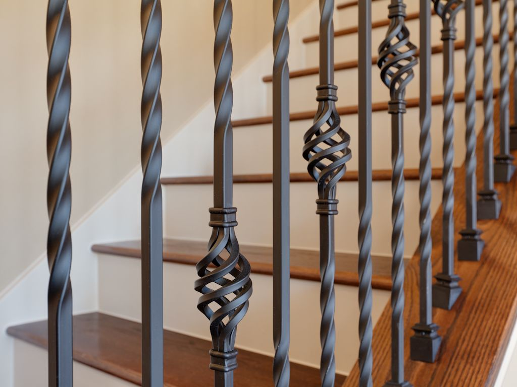 intricate wrought iron stair railing with wood stair tread and white painted stair