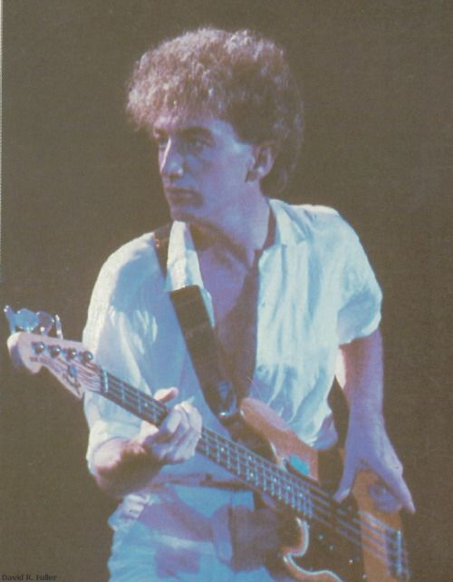 John Deacon playing his bass guitar in concert with Queen (1984)