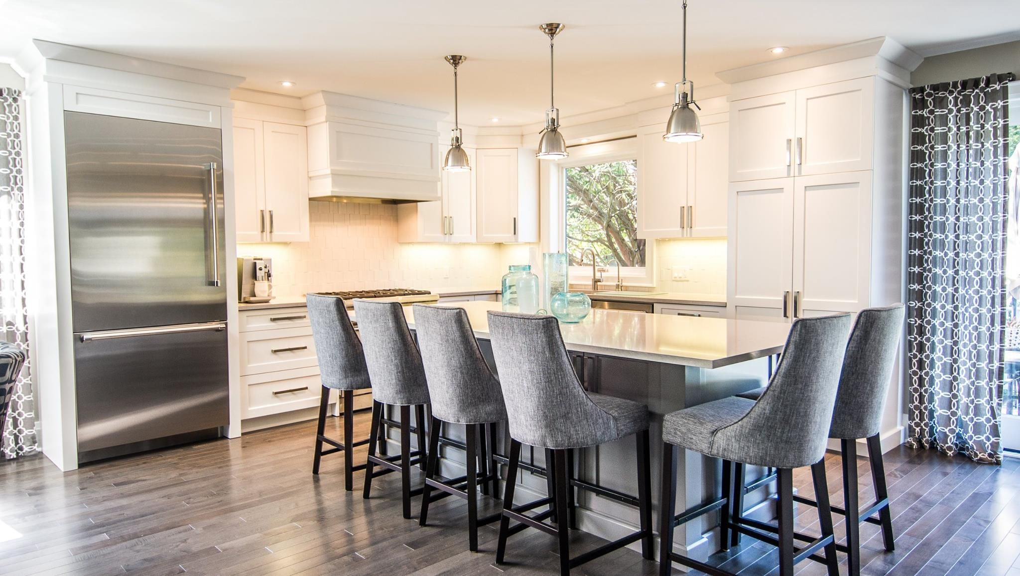 Blackstone Cabinetry pairs soft grey upholstery and curtains with understated Clamshell countertops in this clean and contemporary kitchen design that's a modern take on the classic black and white color combo.