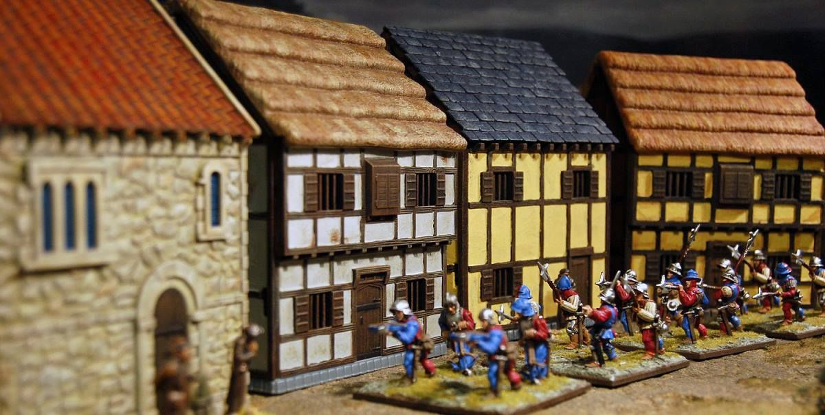 Soldiers charge through a Tabletop Workshop Town containg the two-storey houses and Medieval Chapel.