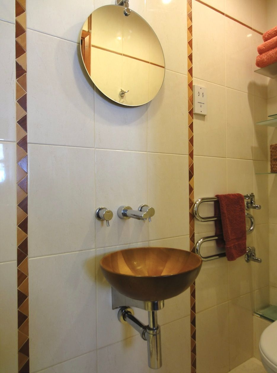 A beautiful wall hung teak basin fits neatly into a small shower ...