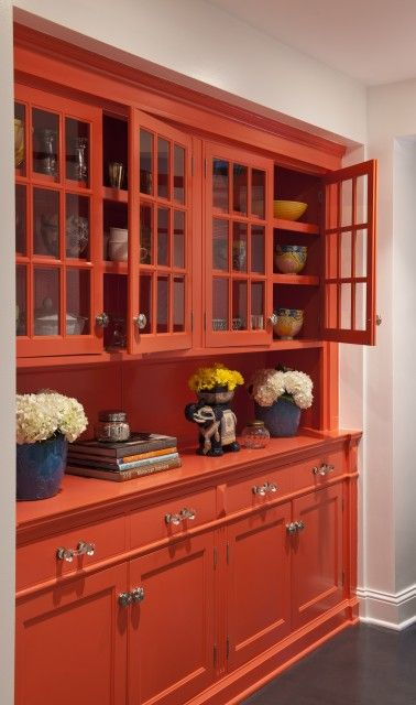 From Lucy Interior Design - Bright orange built-in glass-front cabinets and blue accents.