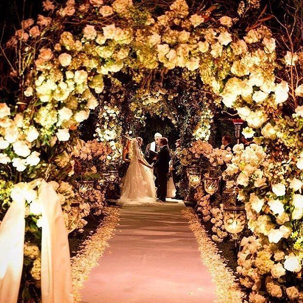 Dreaming of exchanging vows at night? Even more surrounded by flower galore all over the places? Definitely a YES! Our hearts skip a beat the moment we saw this magical ceremony setup! Particularly adore the combination of blooming white flower archs candle arrangement and perfect lighting that builds an intimate and romantic nuance to the place. Don't you want to exchange your vow in this kind of atmosphere too? Tag someone who would love this! Event Design @LevineFoxEvents / Decoration…