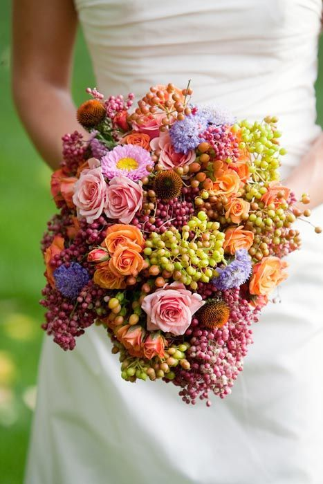 "this bouquet has many repeated shapes, and all of the berries give it a visually heavy look, it seems to be ""spilling"" rather farm-meets-vinyard in a way"