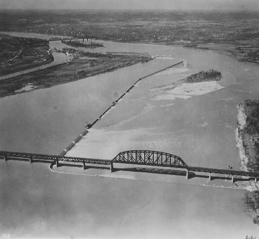 """Portland Canal's Dam 41 in Louisville, Kentucky, and the Falls of the Ohio, where many fossilized organisms can be seen. The river curves right; beyond, it narrows and curves left. Two bridges are shown. Caption on back of image: """"View looking down [], showing general view new dam no. 41 Ohio River. [] house in upper left corner shows lock no. 41 and L Canal."""" Note on back: """"Mr. Newman: Exact location of dam pictures can be obtained at Louisville Dist. Eng offices. They probably have better…"""