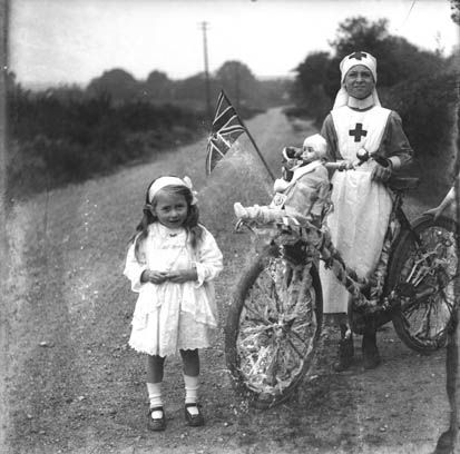 Little girl, nurse, bicycle and doll in around 1915