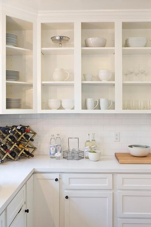 Fabulous White Kitchen Features Upper Cabinets With No Doors Used As Display Shelves Filled Pottery
