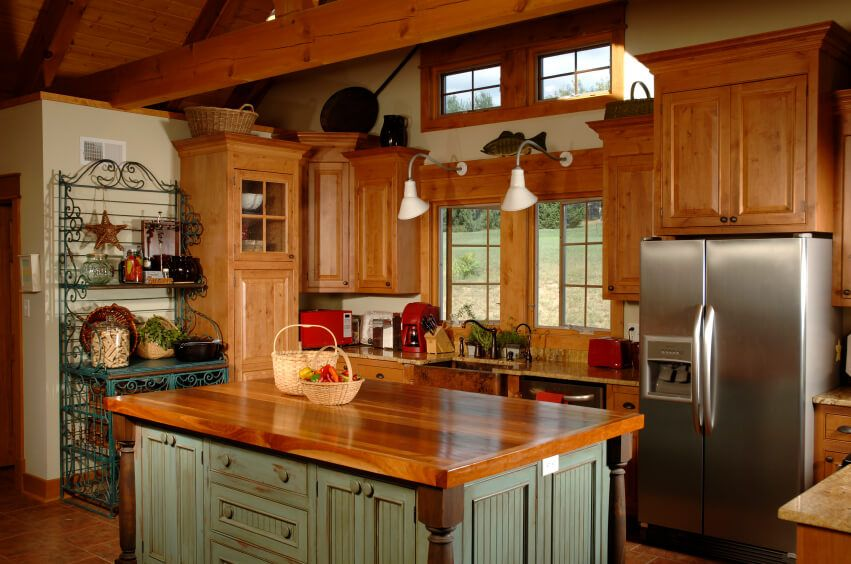 A more contemporary country kitchen with natural wood cabinets that are polished to a sheen. The lower portion of the island is painted a light, muted green and is distressed around the handles. An iron baker's rack sits on the left wall, topped with pottery and other decorative accents. The ceiling is made up of exposed wooden beams that support the vaulted wooden ceiling.