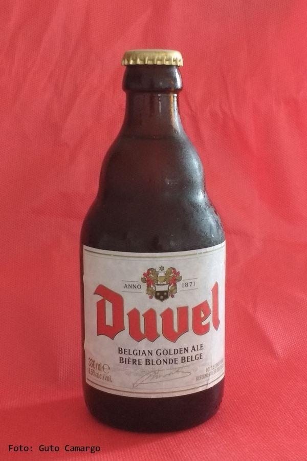 """DUVEL – Uma digna representante das cervejas belgas. Duvel significa diabo pois tem teor alcoólico (8,5%) maior do que a da média. Depois da primeira fermentação ela é engarrafada com uma segunda levedura que continua o processo de fermentação na garrafa, o que forma uma espécie de """"borra"""" no fundo que faz com que os últimos goles sejam ainda mais marcantes. Sua receita peculiar foi criada em 1920 por Albert Moortagat e, segundo a empresa, a levedura selecionada por ele é usada até hoje."""