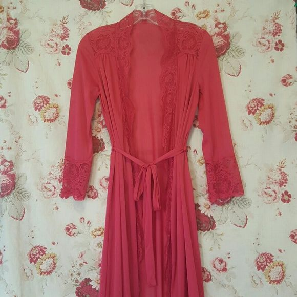 """Vintage raspberry dressing gown Lovely soft robe or ladies dressing gown with lace detail at shoulders, cuffs, and hem. I love the length of the sleeves on this one beacause their 3/4 length allows one to use a sink, apply cream, or do make-up without dragging the cuffs through suds. Perfect addition to an elegant morning routine. Even brushing your teeth will be more glamorous! It is 100% nylon and is marked """"petite."""" I would say it is a modern small but is stretchy enough to accomodate a…"""
