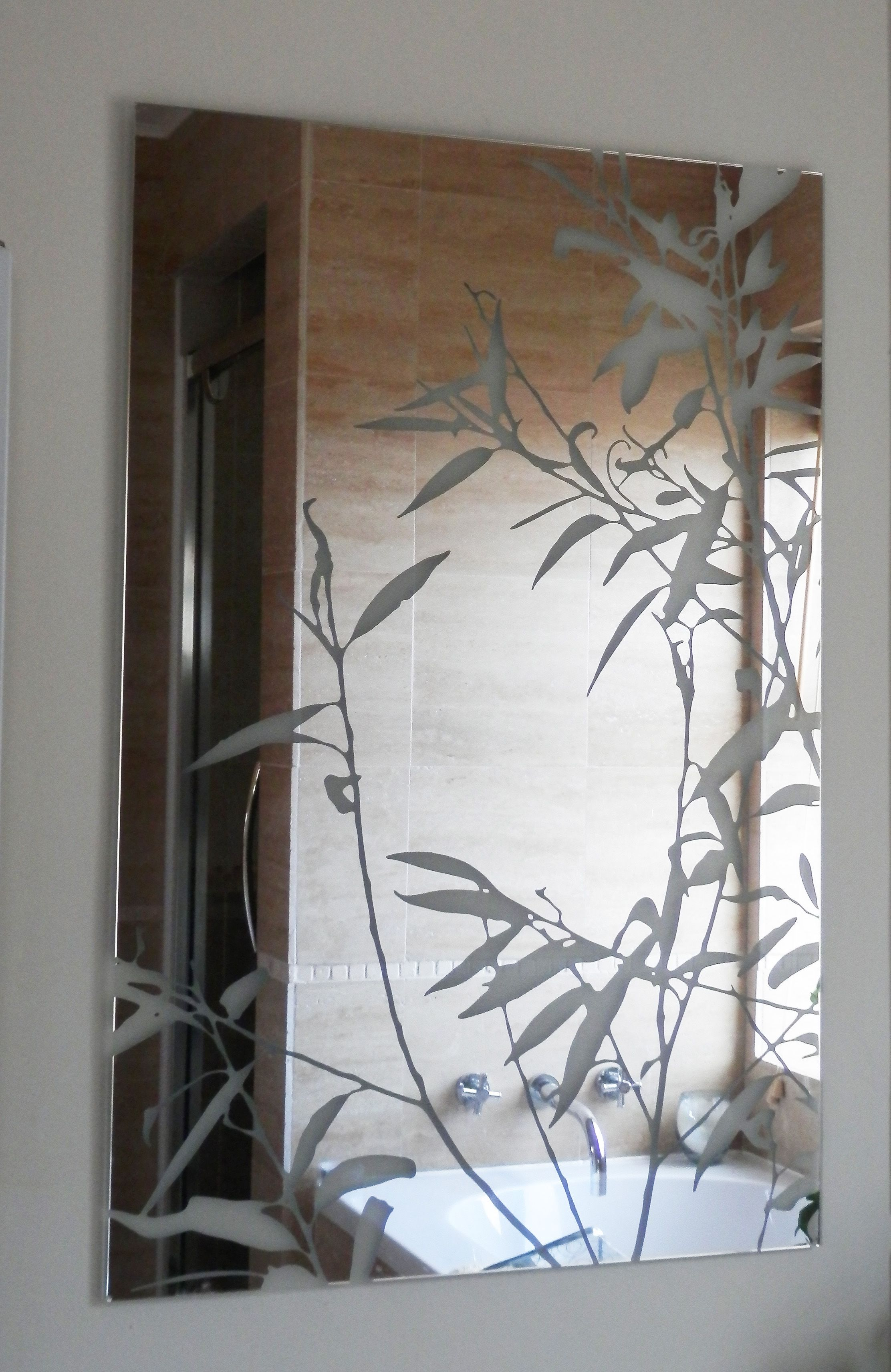 large frameless bathroom mirror with etched willow leaves etched