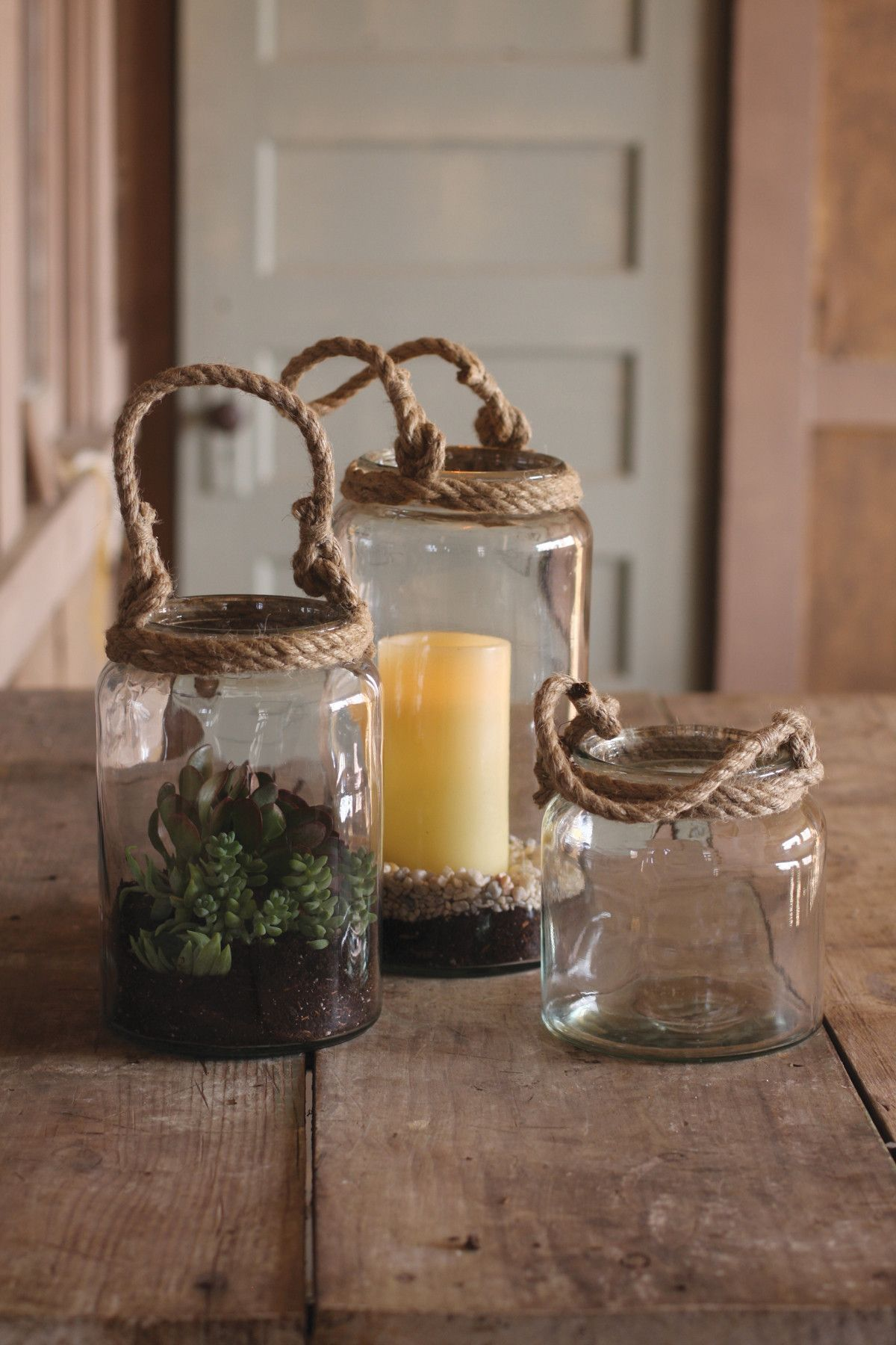 Kalalou Glass Candleholders With Rope Handles - Set Of 3 - With rope handles and a classic shape, these glass jars have an aesthetic that is both rustic and vintage. Dress them up with fresh succulents or illuminate your home with a new candle.