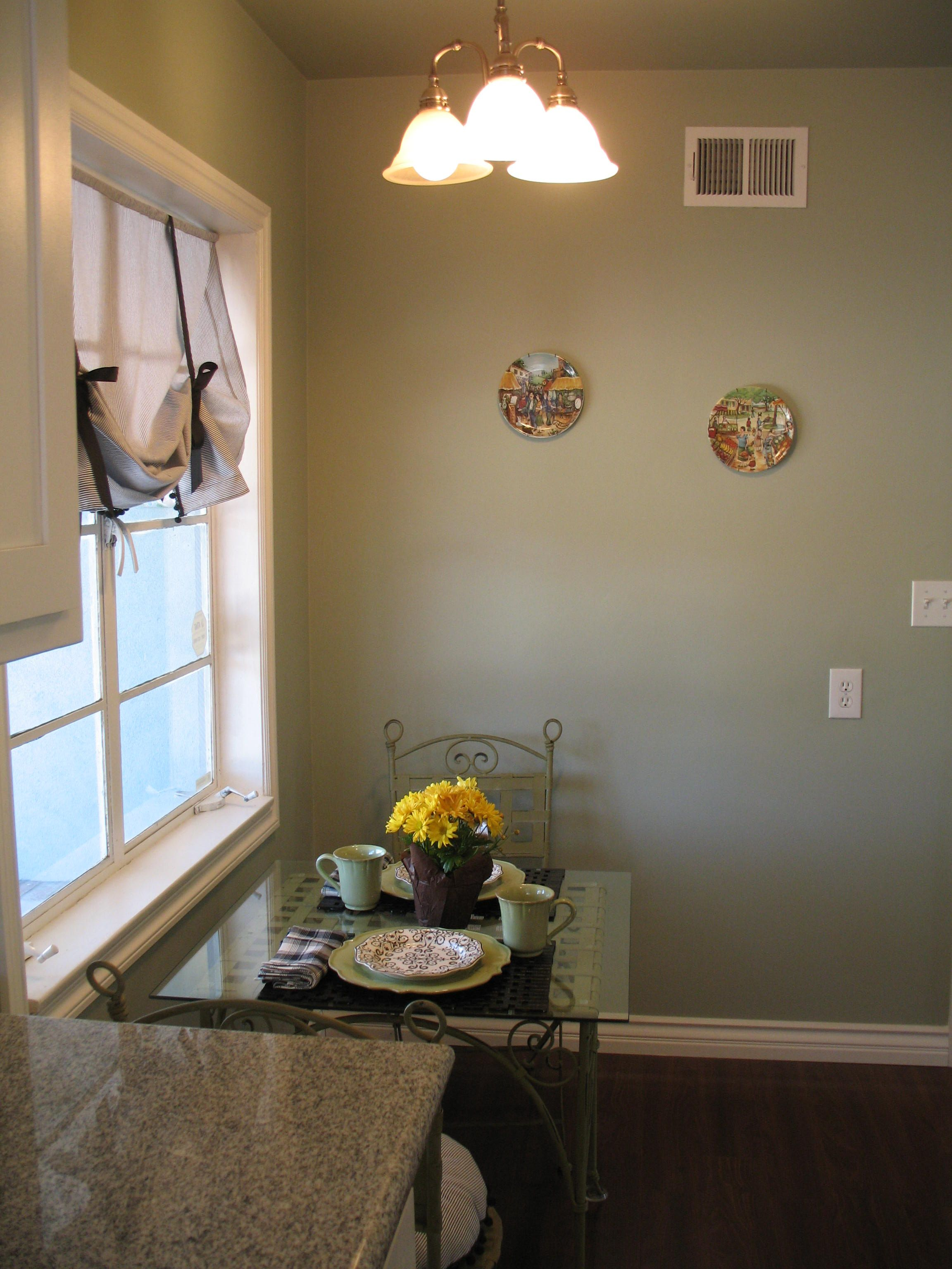 Kitchen after remodel.  I made simple curtains and matching cushions, added some decor and a bistro table adding some glass I found at the property.