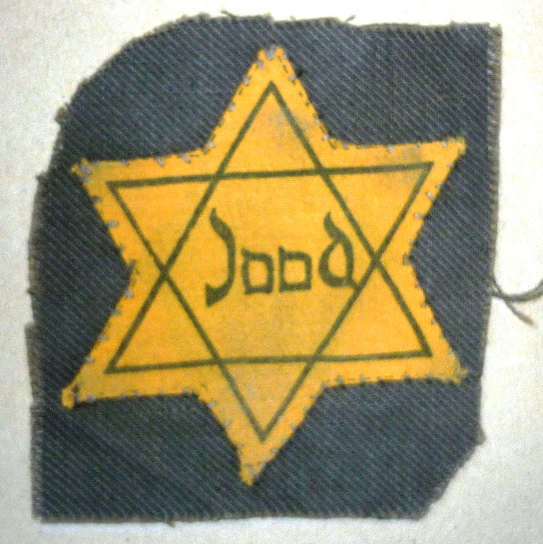 Star of David still attached to the fabric of a coat.
