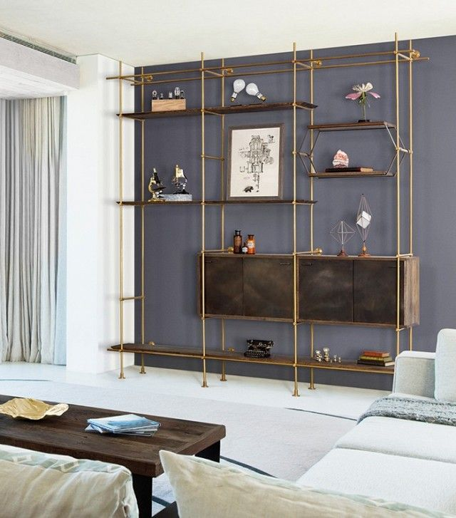 Living Room With A Gray Contrast Wall, And A Copper And Gold Bookshelf