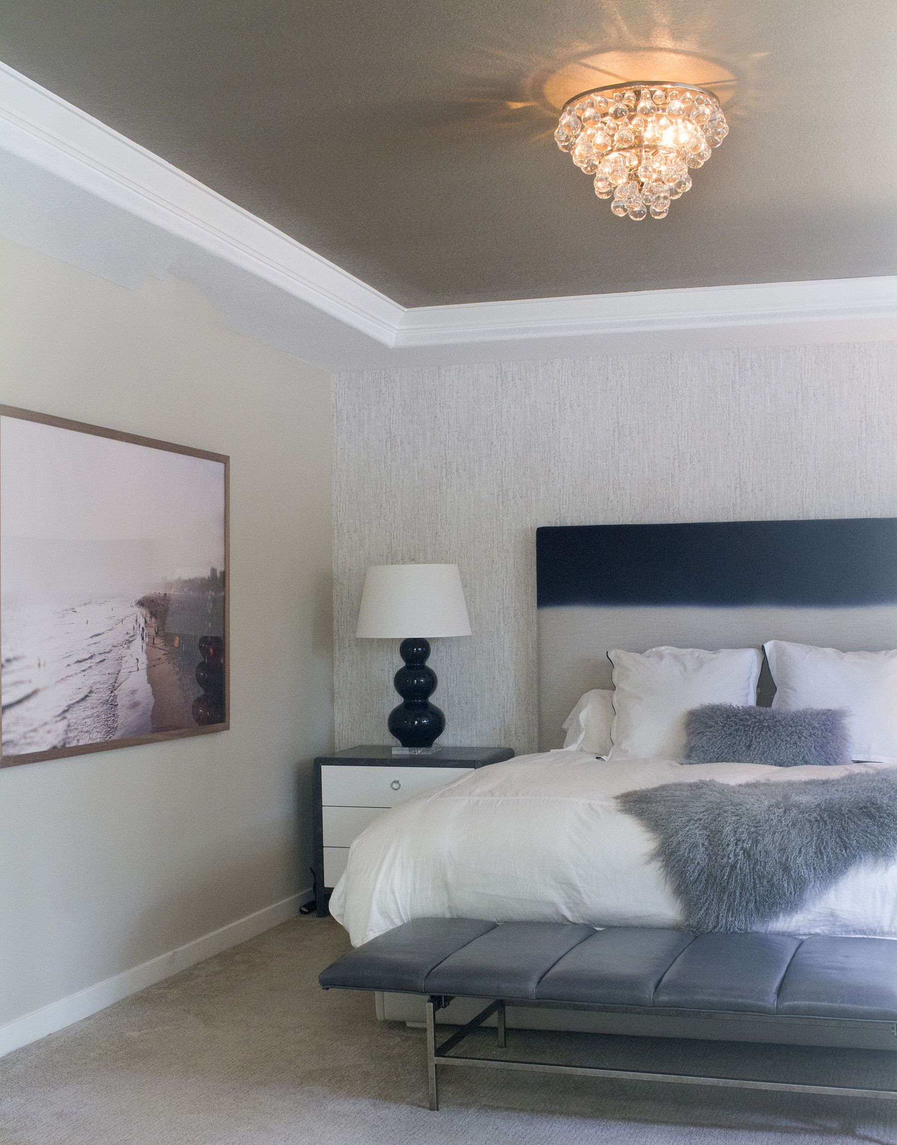 Master bedroom accented by bling chandelier and Jon Rou framed