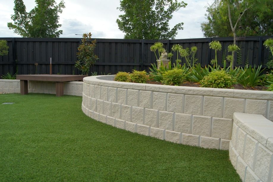 garden simple black fence around large backyard garden landscape with white stoned retaining wall also - Landscape Design Retaining Wall Ideas