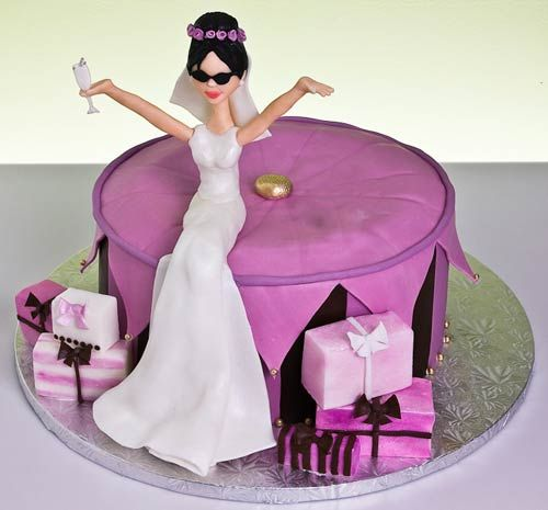 Novelty, round purple bridal shower cake with a bride wedding cake topper. Decorated with small and purple and pink wedding gifts.