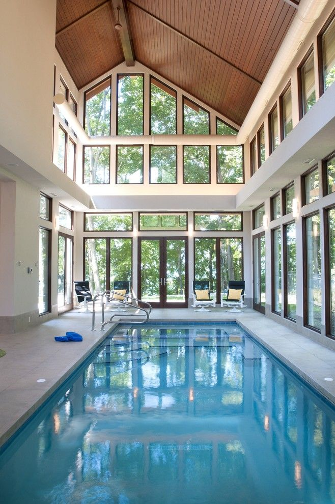 indoor pool wooden ceiling poolside chairs white walls glass windows ...