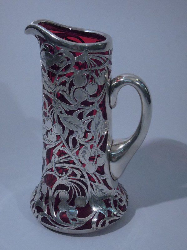 """Cranberry glass jug with sterling silver overlay, C 1900. The jug has a flared bottom, straight sides, and scroll handle. Overlay with foliage and cherries. Engraved monogram (""""R"""") on cartouche. Rim and handle are silver. Nice size with unusual cherry motif."""