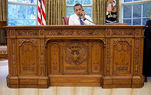 """The Hon. Barack H. Obama working at the the """"Resolute desk"""". This desk is a large, nineteenth-century partners' desk often chosen by presidents of the United States for use in the White House Oval Office as the Oval Office desk. It was a gift from Queen Victoria to President Rutherford B. Hayes in 1880 and was built from the timbers of the British Arctic Exploration ship Resolute. (explanation from Wikipedia)"""