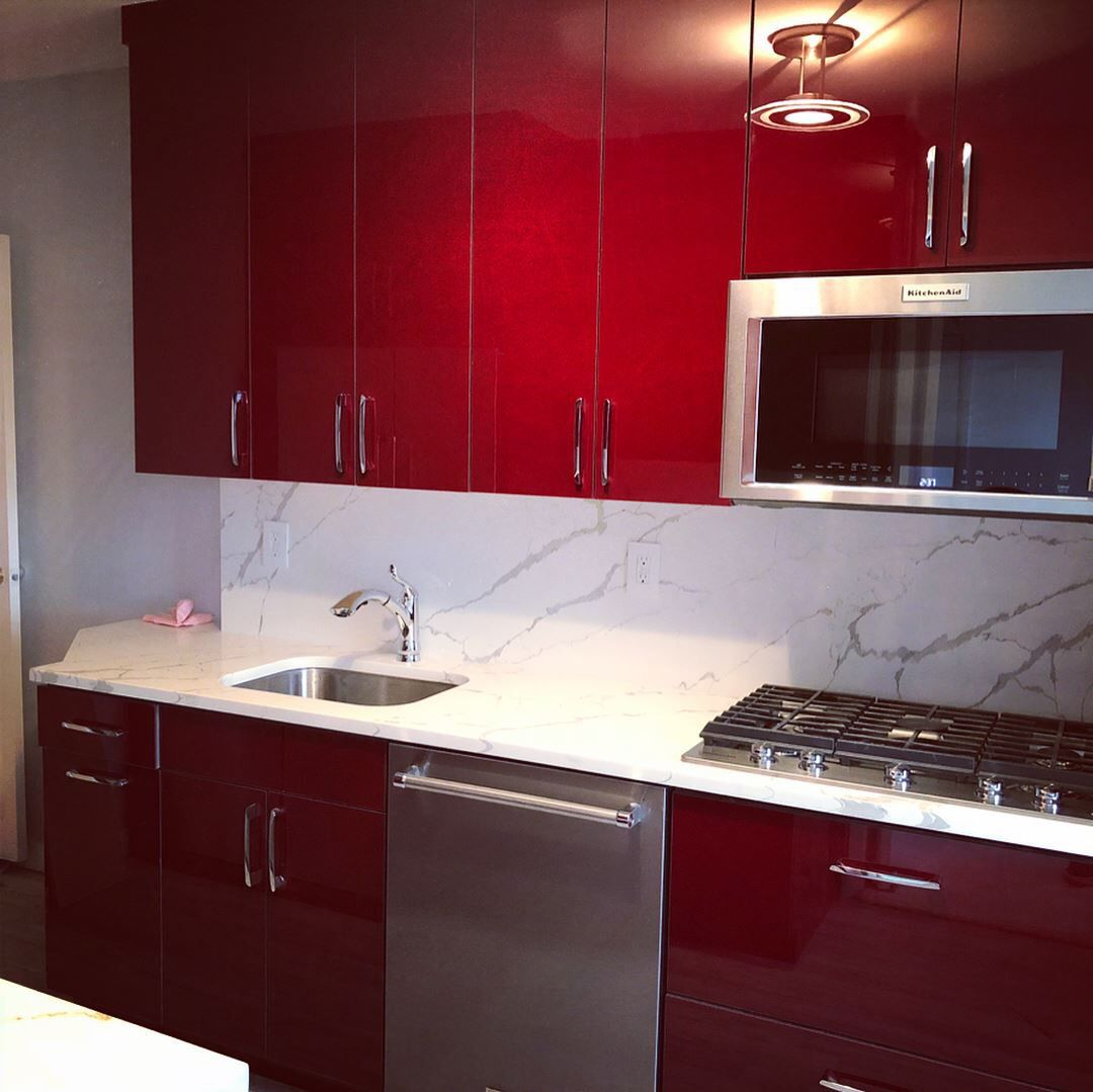 Red Lacquer Kitchen Cabinetry Mixed With Marble Look Quartz