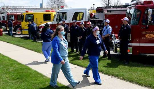 Healthcare workers walk past emergency vehicles during a