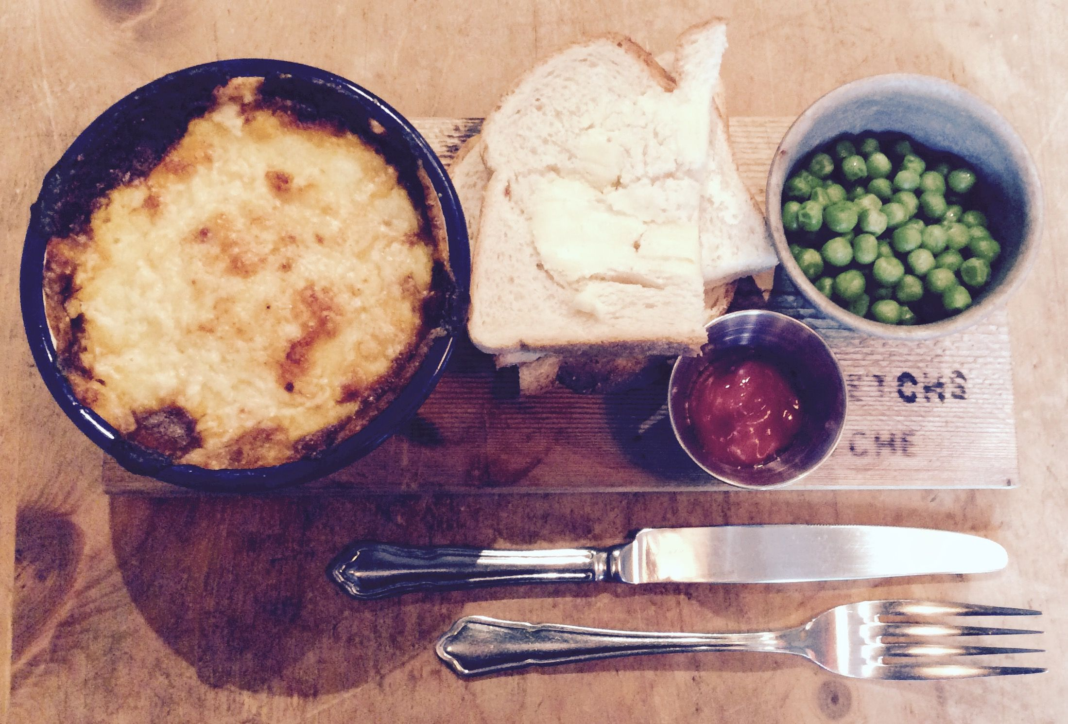 Classic cottage pie (mince, onion, celery,carrot, rosemary, thyme, tom puree, red wine, stock, worcester sauce, topped with mash and cheddar) served with peas, ketchup & bread n butter.