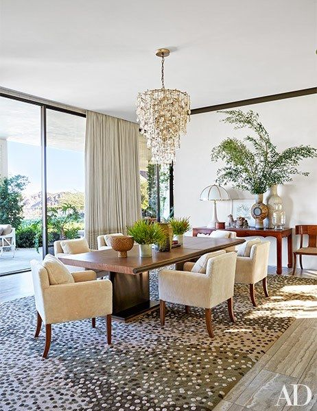 In the dining room, a Jean de Merry light fixture shimmers above a vintage table ringed with shearling-clad chairs | archdigest.com