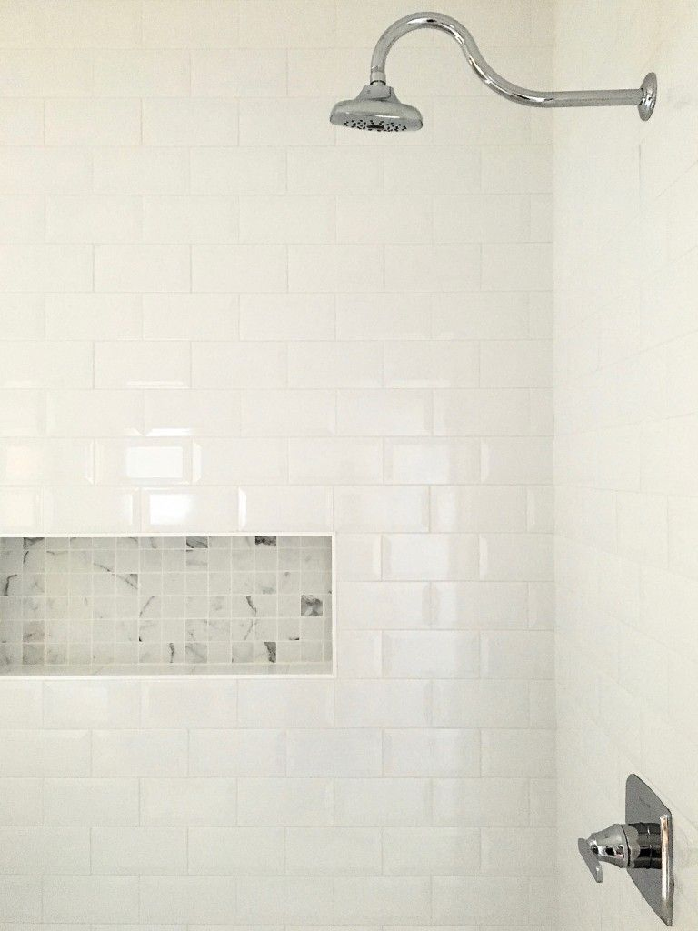 Beveled white subway tiles and Carrera marble accent tiles in the