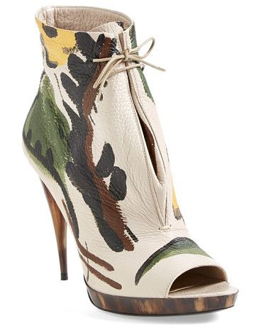 A stunning, one-of-a-kind motif is painted by hand on a supple deerskin bootie lifted by a tapered, horn-detailed heel.
