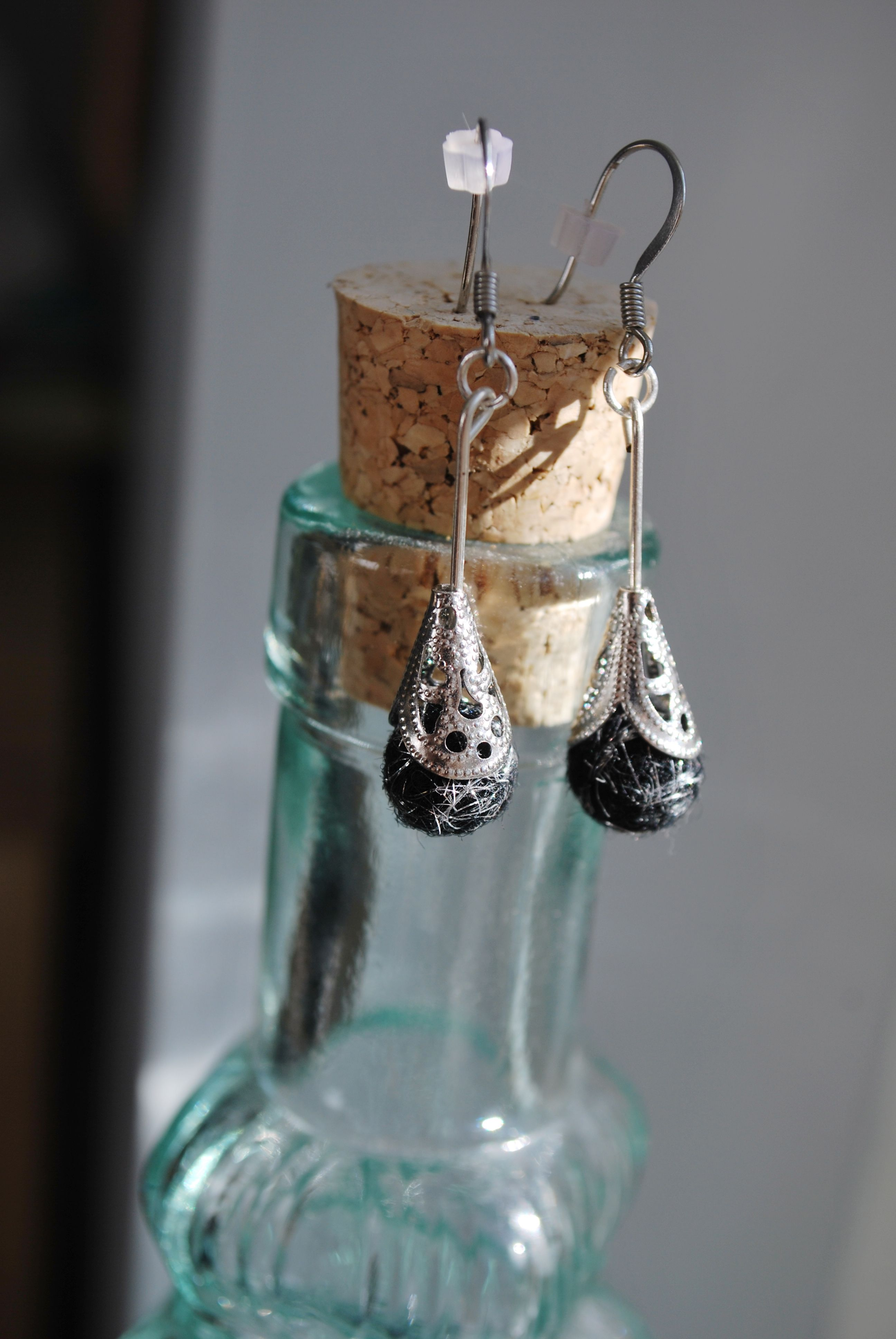 Classic black needle felted earrings. These lovely earrings are mixed with black and metallic silver materials and topped with ornate metal pieces to give that sparkle look.  https://www.etsy.com/shop/ArtByBarks