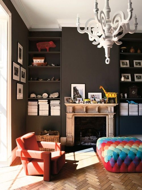 contemporary classic.  moody chocolate walls, contrasting papier mache chandelier, chevron floors, and colorful tufted ottoman.