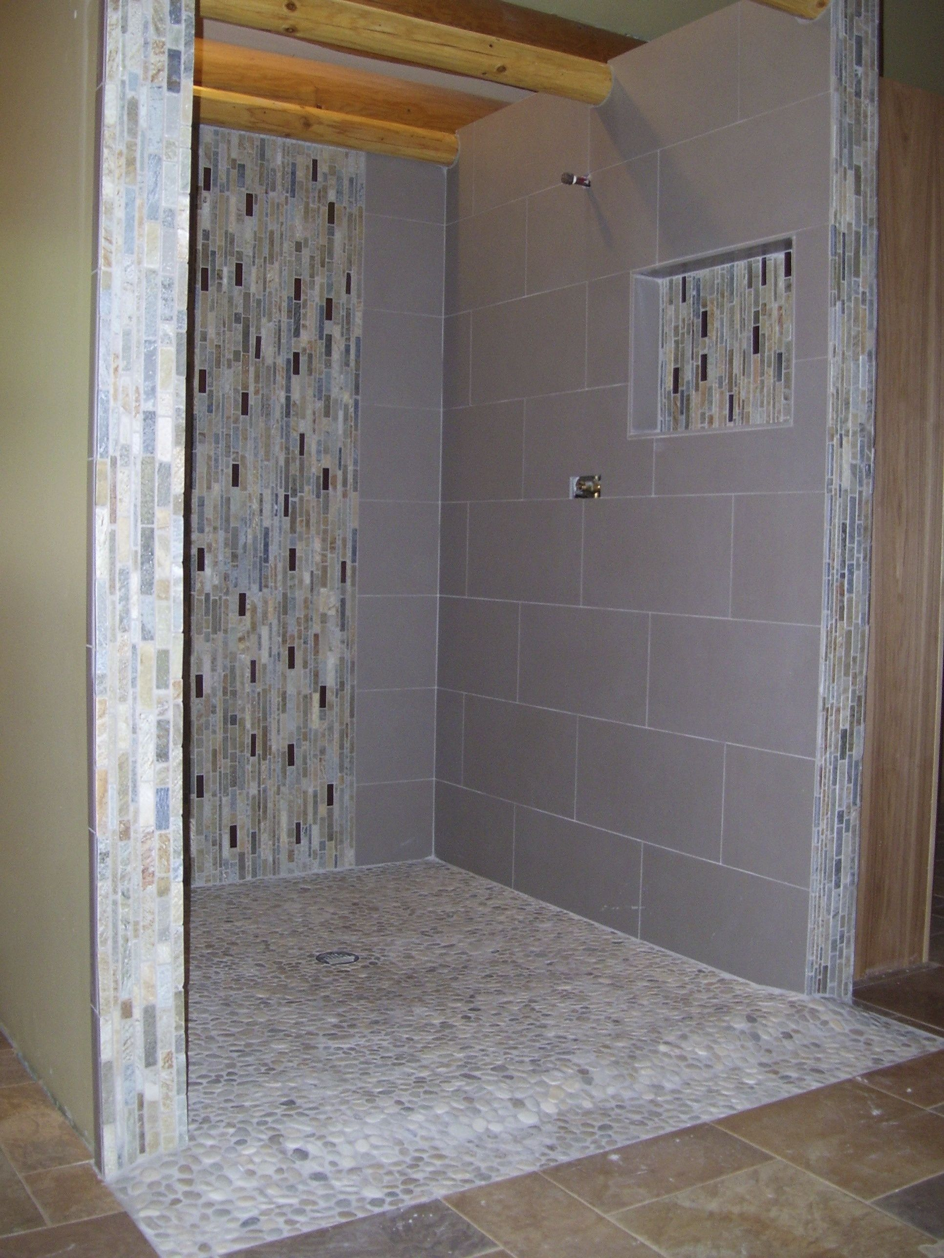 Doorless curbless tile shower with river rock floor and for Rock bathroom designs